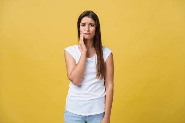 Junge frau hat zahnschmerzen, studiofoto, das auf einem gelben hintergrund lokalisiert wird Premium Fotos