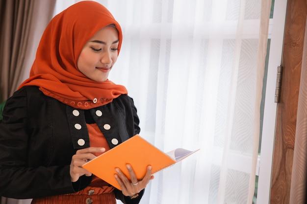 Junge frau hijab hält und schaut ein buch in der nähe von fenstern Premium Fotos