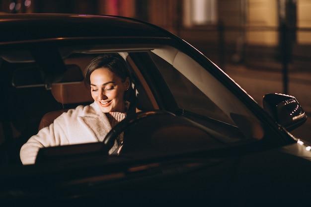 Junge frau im auto, das sicherheitsgurt hält Kostenlose Fotos