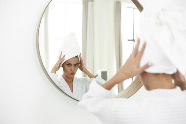 Junge frau im bademantel, der im badezimmerspiegel schaut. pure schönheit. attraktive frau, die ihr gesicht berührt und lächelt, während sie in den spiegel schaut. Premium Fotos