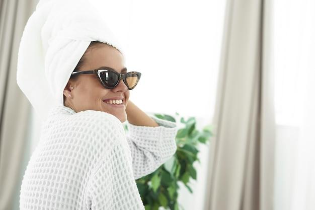 Junge frau im bademantel, mit einem weißen handtuch auf dem kopf und einer schwarzen sonnenbrille, die im badezimmerspiegel schaut. Premium Fotos