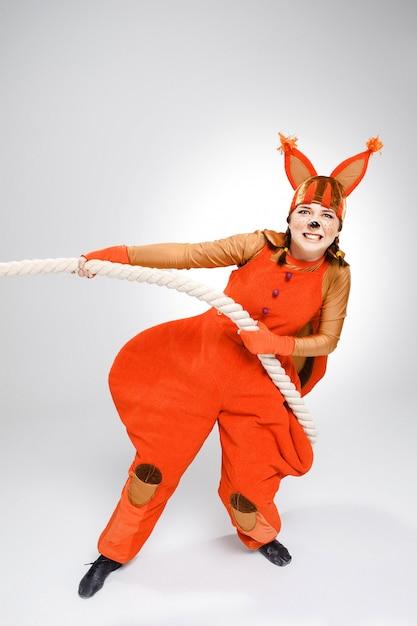Junge frau im bild des roten eichhörnchens, das ein seil zieht Kostenlose Fotos