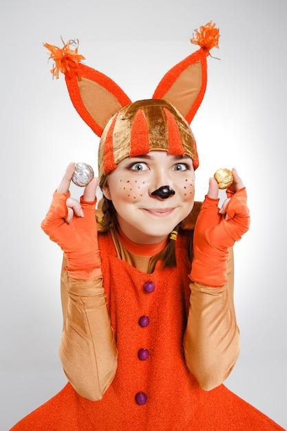 Junge frau im bild des roten eichhörnchens mit walnüssen Kostenlose Fotos