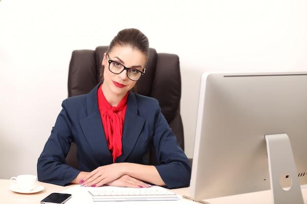 Junge frau im büro, das an dem desktop arbeitet Premium Fotos
