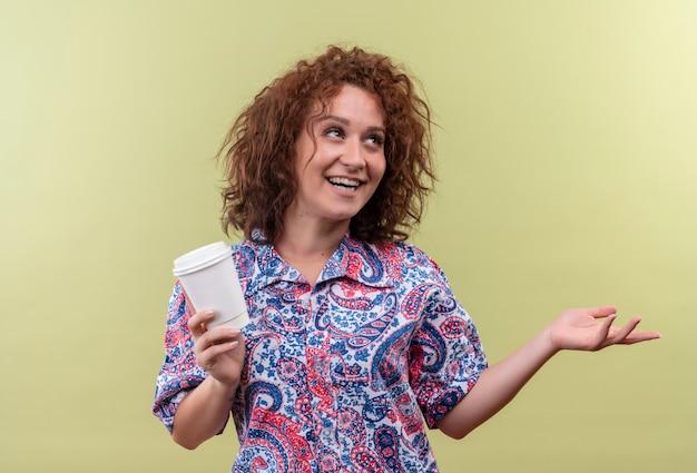 Junge frau im bunten hemd, das kaffeetasse hält, die fröhlich mit arm ihrer hand auf die seite zeigt, die über grüner wand steht Kostenlose Fotos