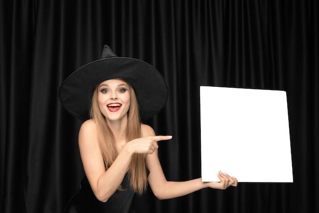 Junge frau im hut als hexe, die leeres brett gegen schwarze vorhänge hält Kostenlose Fotos
