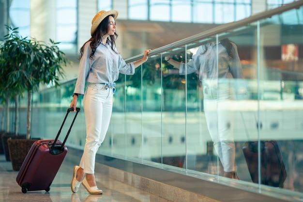 Junge frau im hut mit gepäck im internationalen flughafen. Premium Fotos