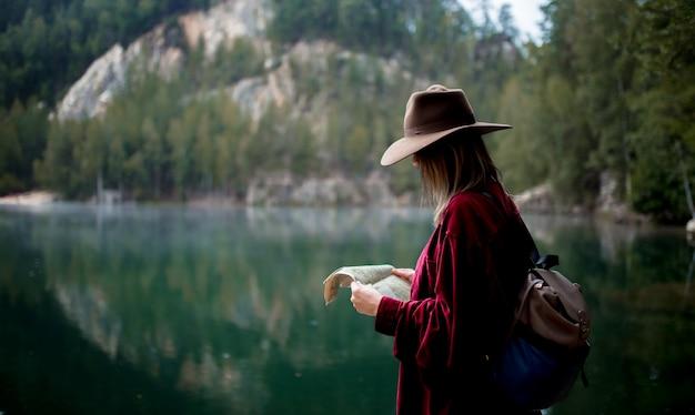 Junge frau im hut und im roten hemd mit karte nahe see Premium Fotos