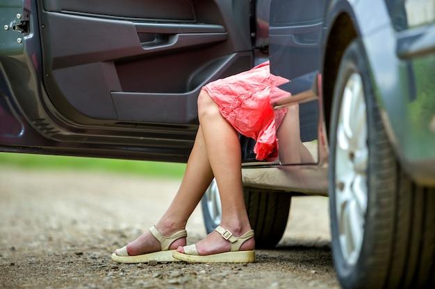 Junge frau im kurzen kleid, das auto mit offener tür auf sonnigem unscharfem landstraßehintergrund hinausgeht. Premium Fotos
