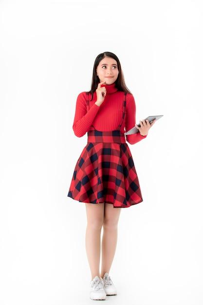 Junge frau im netten roten kleid mit tablette. Premium Fotos