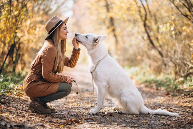 Junge frau im park mit ihrem weißen hund Kostenlose Fotos