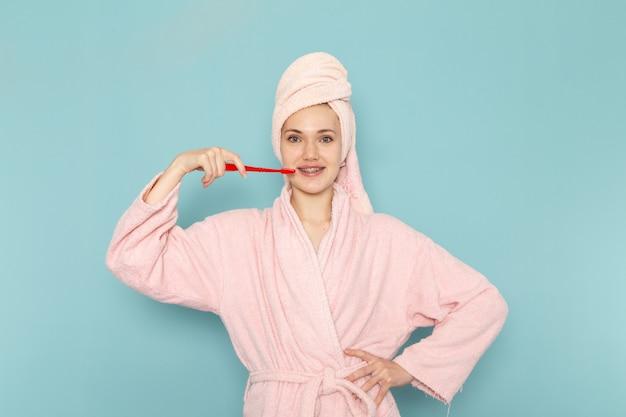 Junge frau im rosa bademantel nach der dusche, die ihre