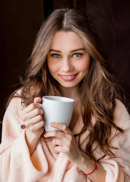 Junge frau im rosa zarten bademantel trinken tee und lächelnd. Kostenlose Fotos