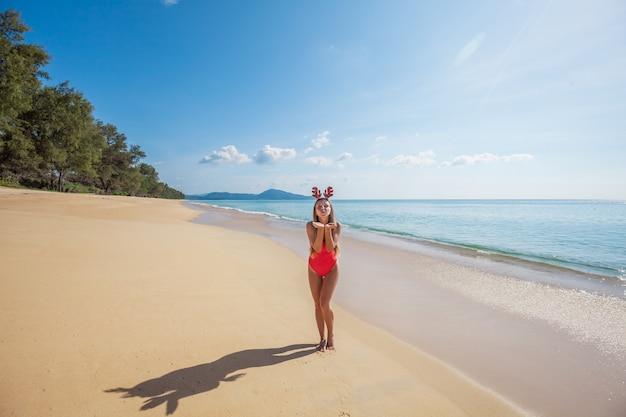 Junge frau im roten badeanzug, der die lustigen weihnachtsrengeweihe senden luftkuß auf dem strand trägt Premium Fotos