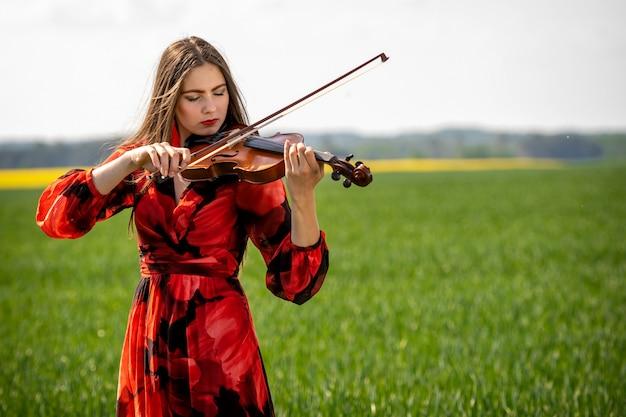 Junge frau im roten kleid, das violine in der grünen wiese spielt Premium Fotos