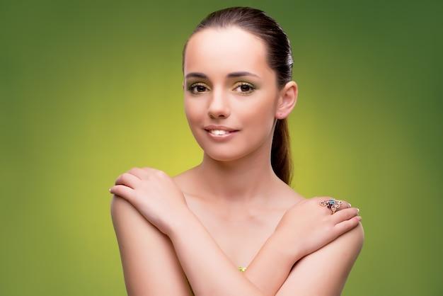 Junge frau im schönheitskonzept auf grüner wand Premium Fotos