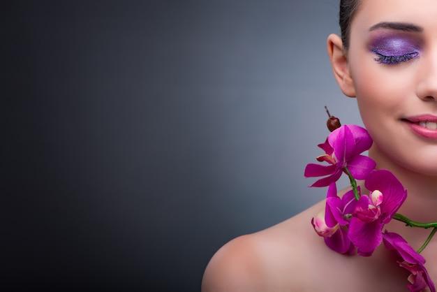 Junge frau im schönheitskonzept mit orchideenblume Premium Fotos