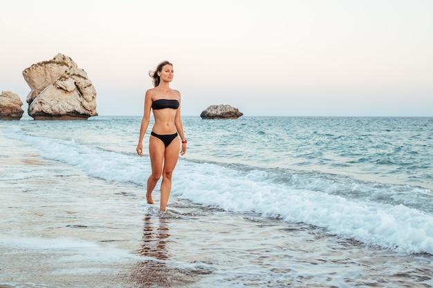 Junge frau im schwarzen bikini am strand Premium Fotos