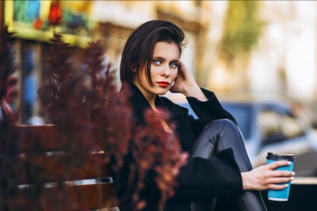 Junge frau im schwarzen mantel, sitzt auf einer bank in der stadt und hält eine tasse kaffee. Premium Fotos
