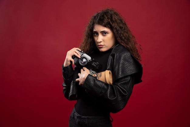 Junge frau im schwarzen outfit, das eine tasse und eine kamera hält. Kostenlose Fotos