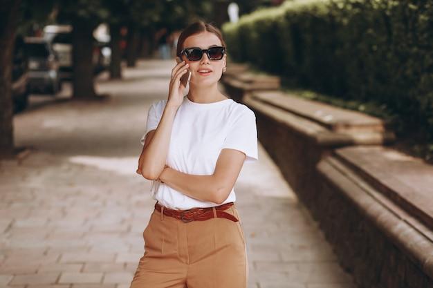 Junge frau im stadtzentrum sprechend am telefon Kostenlose Fotos
