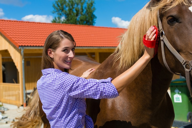 Junge frau im stall mit pferd Premium Fotos