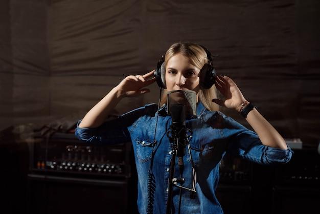 Junge frau im tonstudio sprechend in mikrofon. Premium Fotos