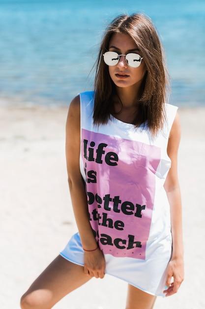 Junge frau im übergroßen trägershirt auf strand Kostenlose Fotos