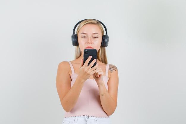 Junge frau im unterhemd, minirock, kopfhörer, die auf videoanruf sprechen Kostenlose Fotos