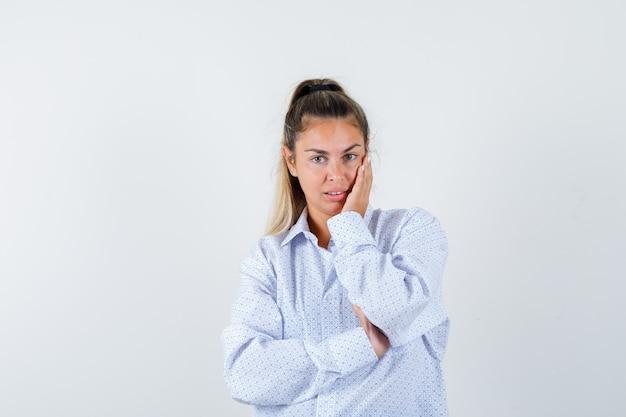 Junge frau im weißen hemd, das wange auf handfläche lehnt, während sie aufwirft und fröhlich schaut Kostenlose Fotos