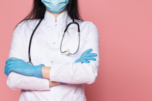 Junge frau im weißen medizinischen anzug blaue handschuhe blaue schutzmaske mit stethoskop auf rosa Kostenlose Fotos