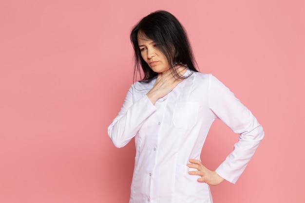 Junge frau im weißen medizinischen anzug, der atemprobleme auf rosa hat Kostenlose Fotos