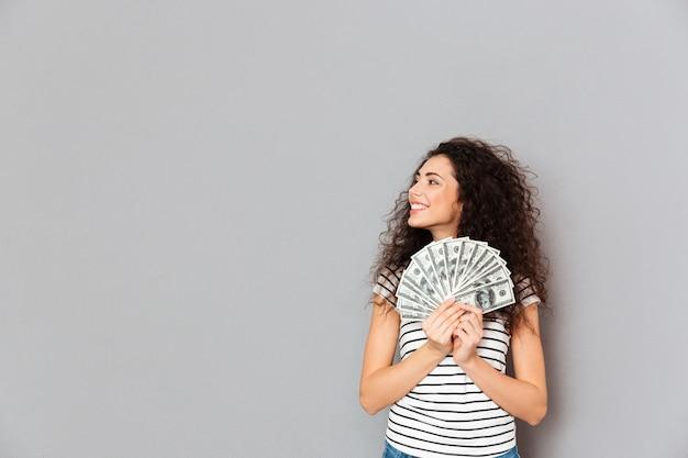 Junge frau im zufälligen haltenen fan von 100 dollarscheinen in den händen, die beiseite mit dem breiten lächeln ist froh über grauer wand schauen Kostenlose Fotos