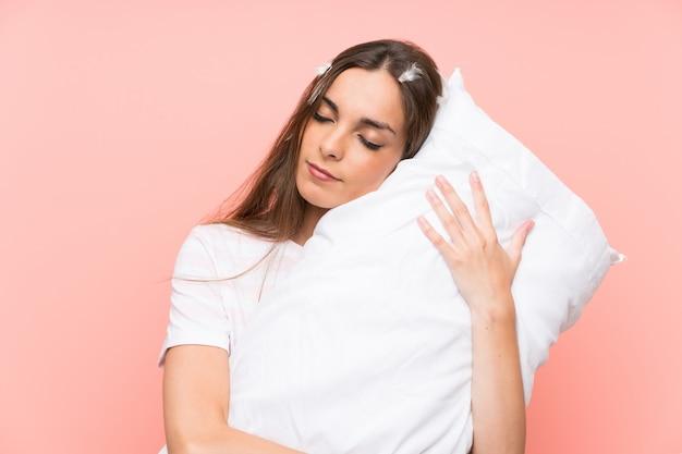 Junge frau in den pyjamas über getrennter rosafarbener wand Premium Fotos
