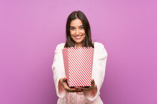Junge frau in den pyjamas und im hausmantel über dem lokalisierten purpurroten hintergrund, der popcorn hält Premium Fotos