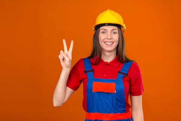 Junge frau in der bauuniform und im gelben sicherheitshelm, der das lächelnde siegeszeichen nummer zwei zeigt, das auf orange hintergrund steht Kostenlose Fotos