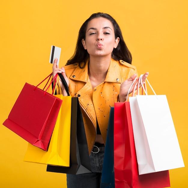Junge frau in der gelben lederjacke mit einkaufstaschen Kostenlose Fotos