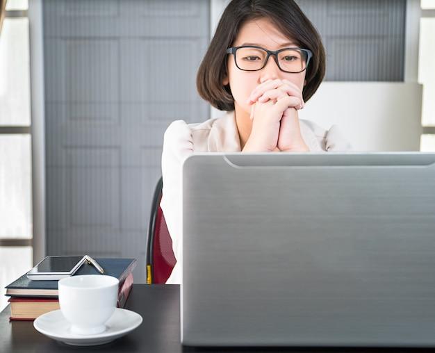 Junge frau in der intelligenten freizeitkleidung, die an laptop arbeitet Premium Fotos