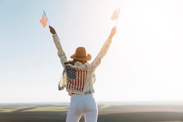 Junge frau in der jacke der amerikanischen flagge auf berg Kostenlose Fotos