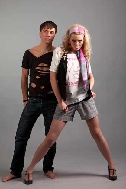 Junge frau in der rosa kleidung, die jungen mann in schwarz von hinten über gey hintergrund im fotostudio umarmt. beauty- und fashion-lifestyle-konzept Premium Fotos