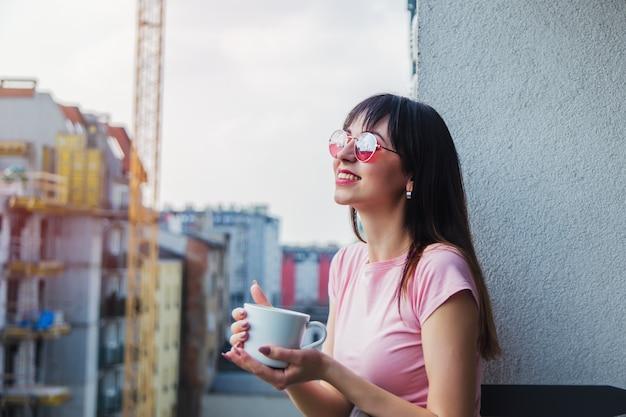 Junge frau in der sonnenbrille mit tasse kaffee bleiben auf balkon Premium Fotos