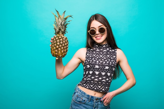 Junge frau in der sonnenbrillen-freizeitkleidung mit ananas in den händen lokalisiert Kostenlose Fotos