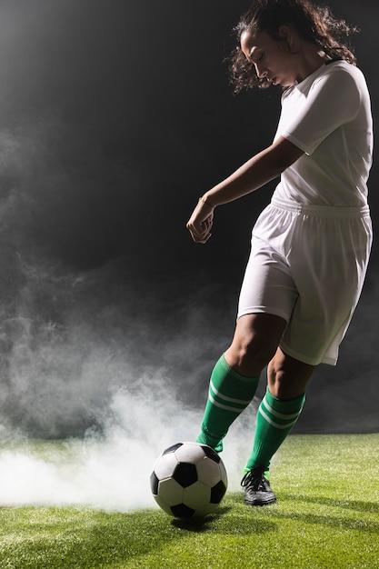 Junge frau in der sportkleidung, die fußball spielt Kostenlose Fotos
