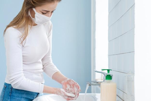 Junge frau in der sterilen medizinischen schutzmaske, die ihre hände wäscht Kostenlose Fotos