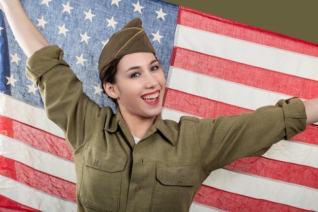 Junge frau in der us-militäruniform, die eine amerikanische flagge hält. Premium Fotos