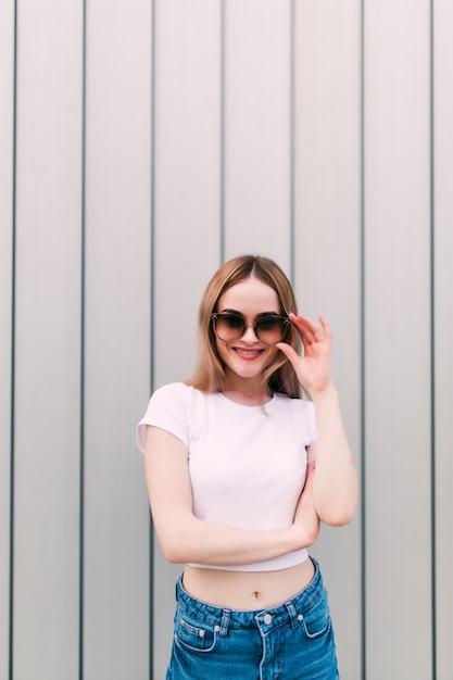 Junge frau in der vintage-sonnenbrille in der stilvollen markenkleidung nahe einer gestreiften metallwand Kostenlose Fotos