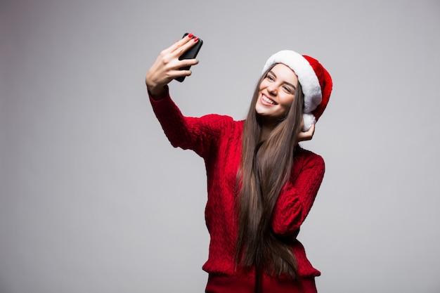 Junge frau in der weihnachtsmütze nehmen selfie am telefon lokalisiert auf grauer wand Kostenlose Fotos