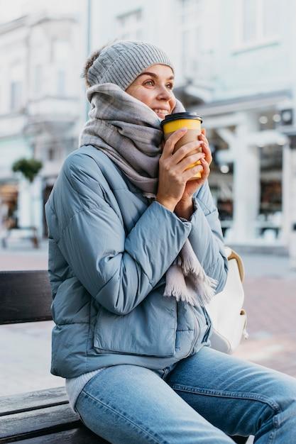 Junge frau in der winterkleidung, die eine tasse kaffee hält Kostenlose Fotos