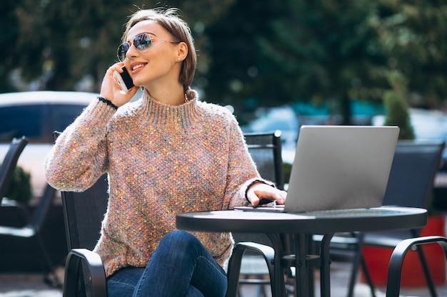 Junge frau in einem café unter verwendung des laptops Kostenlose Fotos