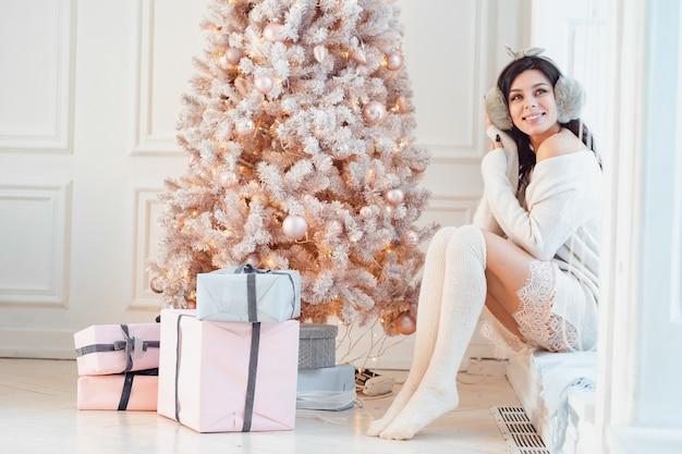 Junge frau in einem eleganten kleid nahe dem weihnachtsbaum Kostenlose Fotos